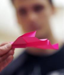 A student checks out a paper airplane Wednesday, April 24, 2013, in Pittsburgh.