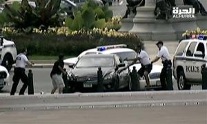 This image from video provided by Alhurra Television shows police with guns drawn surrounding a black Infiniti near the U.S. Capitol in Washington, Thursday, Oct. 3, 2013.
