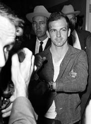 Lee Harvey Oswald holds up his manacled hands at police headquarters in Dallas, Texas, where he is held for questioning, in this Nov. 22, 1963 file photo.