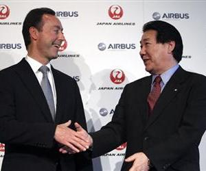 Airbus Japan Chief Executive Fabrice Bregier, left, and  Japan Airlines President Yoshiharu Ueki shake hands following their press conference in Tokyo, Monday, Oct. 7, 2013.