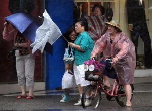 Taiwanese women hold their umbrellas against powerful gusts of wind as Typhoon Fitow approaches in Taipei, Taiwan, Sunday, Oct. 6, 2013.