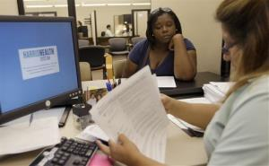 Lillian Ardon, right, a certified application counselor with Harris Health System, helps Vanessa Danielle Cotton, left, with her Affordable Care Act application in Houston.