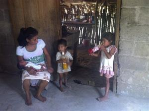 In this Oct. 6, 2013 photo, 29-year-old Irma Lopez talks to her children as her newborn son Salvador sleeps on her lap at her home in the town of Jalapa de Diaz, Mexico.