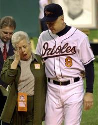 This Oct. 6, 2001 file photo shows Cal Ripken escorting his mother, Vi, from the field, after throwing out the ceremonial first pitch before Cal's final game, at Oriole Park in Baltimore.