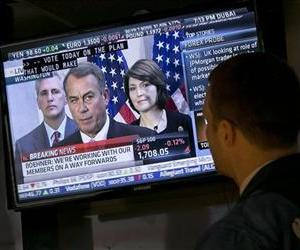 A specialist watches a television monitor on the floor of the New York Stock Exchange showing a Washington news conference by House Speaker John Boehner, Tuesday, Oct. 15, 2013.