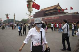 This is a May 7, 2013 file  photo of  a foreign tourist wearing a mask walks in front of Tiananmen Gate on a polluted day in Beijing, China.