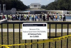 In this Oct. 2, 2013 file photo people visit the closed World War II Memorial on the National Mall in Washington, despite signs stating that the national parks are closed due to the federal shutdown.