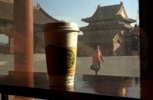 A tourist walks past the windows to an outlet of Starbucks at the Forbidden City in Beijing, China.