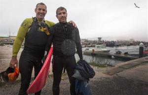Surfers Carlos Burle, right, from Brazil, and Garrett McNamara, from the US, pose for a photo after Burle surfed a giant wave at Nazare on Portugal's Atlantic coast yesterday.