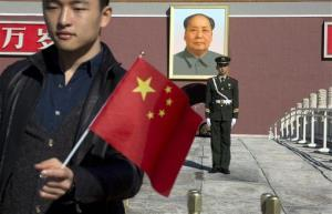 A tourist holds up a Chinese flag as he poses for photos near a Chinese paramilitary policeman on duty in front of former Chinese leader Mao Zedong's portrait on Tiananmen Gate.