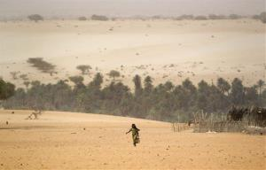 A young girl carries an empty container as she walks across the sands to fill it from a well in Barrah, a desert village in the Sahel belt of Chad, Friday, April 20, 2012. UNICEF estimates that 127,000 children under 5 in Chad's Sahel belt will require lifesaving treatment...