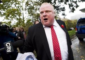 Toronto Mayor Rob Ford  tells the media to get off his property as he leaves his home in Toronto on Thursday.