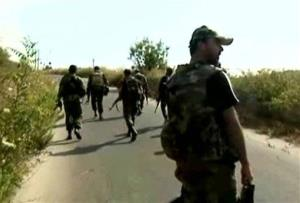 In this image released by the Syrian official news agency SANA, Syrian army soldiers walk on a street at an unidentified location in Latakia province, Syria, Tuesday, Aug. 13, 2013.