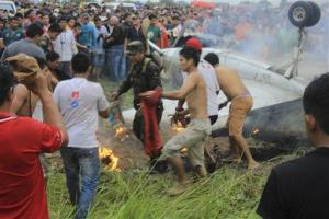 People try to extinguish the fire after the crash near the airport in Riveralta, Beni province, Bolivia.
