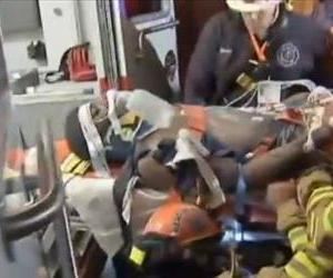 Asher Vongtau is wheeled into an ambulance in this screenshot from a television report.