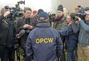 Franz Ontal, OPCW's head of inspector training, center, talks with journalists after a training session with UN inspectors of the Organization for the Prohibition of Chemical Weapons.