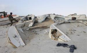 In this Sept. 23, 2012, file photo, a Somali government soldier walks next to some of the overturned pirate skiffs that litter the dunes on the shoreline near the once-bustling pirate den of Hobyo.
