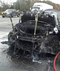 In this photo provided by the Tennessee Highway Patrol, emergency workers respond to a fire on a Tesla Model S electric car in Smyrna, Tenn.