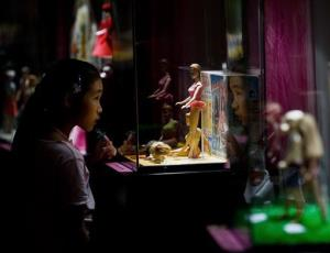 A young Chinese girl looks at the Barbie dolls on display at a Barbie dolls exhibition held in Beijing, China, Thursday, April 30, 2009.