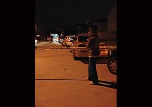 An unidentified parent waits on a child at the scene of a suburban Houston shooting early Sunday Nov. 10, 2013. Two people have been killed and at least 22 others hurt when gunfire rang out at the large house party in the Cypress-area of Houston, sending partygoers fleeing in panic,...