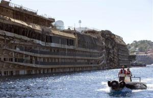 In this Sept. 18, 2013 file photo, a small boat navigates past the damaged side of the Costa Concordia ship after it was pulled upright, on the Tuscan Island of Giglio, Italy.