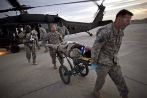 US Army medical staff wheel an Afghan interpreter injured while working with U.S. Marines off a medevac helicopter.