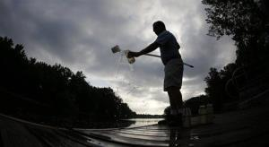 In this  July 26, 2013, photo, Des Moines water works lab technician Bill Blubaugh takes a water sample from the Des Moines River.