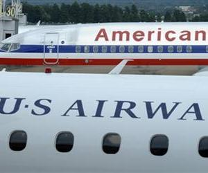 This Aug. 13, 2013, file photo shows an American Airlines plane and a US Airways plane at parked at Washington's Reagan National Airport.
