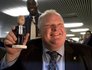 Toronto Mayor Rob Ford holds a Rob Ford bobblehead doll at Toronto city hall on Tuesday, Nov. 12, 2013.
