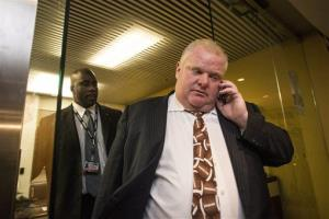 Toronto Mayor Rob Ford talks on his cell phone as he makes his way to the council chamber in Toronto yesterday.
