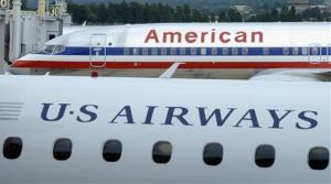 This Tuesday, Aug. 13, 2013 file photo shows an American Airlines plane and a US Airways plane at parked at Washington's Ronald Reagan National Airport.