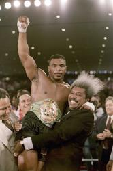 In this Nov. 22, 1986, file photo, boxing promoter Don King lifts new heavyweight champion Mike Tyson after Tyson defeated Trevor Berbick in Las Vegas.