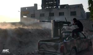 In this Saturday, Nov. 9, 2013 citizen journalism image, a Syrian rebel fires a weapon towards Syrian government troops loyal to President Bashar Assad in Aleppo, Syria.