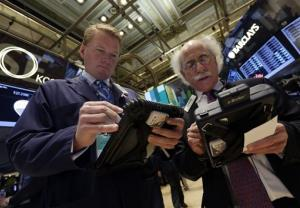 FILE - In this Tuesday, Nov. 12, 2013, file photo, traders John Bowers, left, and Peter Tuchman work on the floor of the New York Stock Exchange.