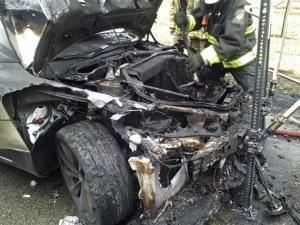 In this Wednesday, Nov. 6, 2013 file photo provided by the Tennessee Highway Patrol, emergency workers respond to a fire on a Tesla Model S electric car in Smyrna, Tenn.