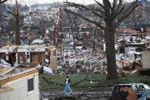 A man walks through what is left of a neighborhood in Washington, Ill., Monday.