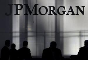 People are silhouetted below signage at the JPMorgan Chase & Co. headquarters in New York, Tuesday, Nov. 19, 2013.