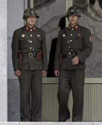 Two North Korean soldiers watch the south side of the border village of Panmunjom in this file photo.