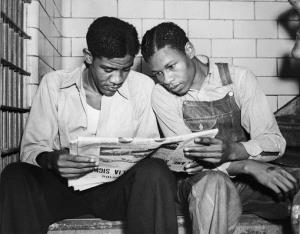 In this July 16, 1937 file photo, Charlie Weems, left, and Clarence Norris, Scottsboro case defendants, read a newspaper in their Decatur, Ala. jail.