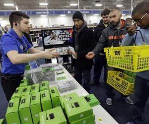 Nikolai Vacca, left, explains the newest XBox One accessories to customers at a Best Buy store on Friday, Nov. 22, 2013, in Evanston, Ill.