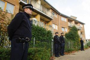Police officers stand outside flats as police conduct house-to-house inquires in the area where three women were rescued in south London, Saturday, Nov. 23, 2013.