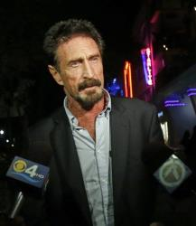 Anti-virus software founder John McAfee answers questions to reporters as he walks on Ocean Drive in the South Beach area of Miami Beach, Fla., Wednesday, Dec 12, 2012.