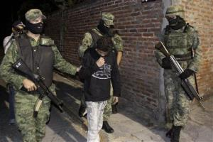 In this Dec. 3, 2010 file photo, Mexican soldiers present Edgar El Ponchis Jimenez Lugo to the media in the city of Cuernavaca, Mexico.