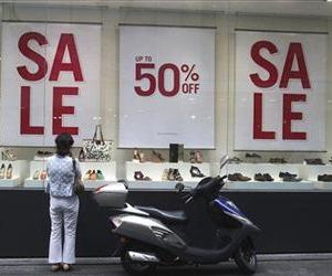 A shopper looks into the show window during a discount sale at a store in Seoul, South Korea, Friday, July 13, 2012.