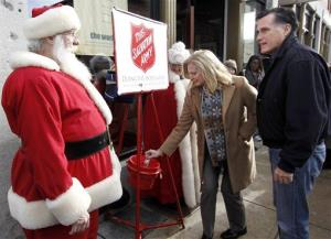 Mitt Romney, right,  talks with a bell ringer as his wife Ann puts money into a Salvation Army kettle while campaigning in Concord, NH Friday, Dec. 23, 2011.