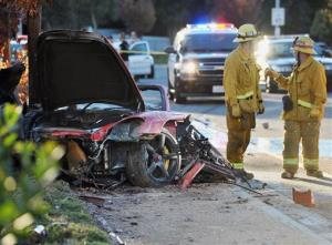 First responders gather evidence near the wreckage of a Porsche sports car that crashed into a light pole on Hercules Street near Kelly Johnson Parkway in Valencia on Saturday, Nov. 30, 2013.