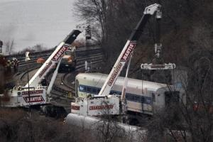 Cranes lift a derailed Metro-North train car, Monday, Dec. 2, 2013, in the Bronx borough of New York.