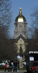 People walk in front of the Notre Dame administration building, known as the Golden Dome.