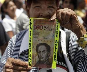 In this February file photo, a protester in Caracas holds up a fake Venezuelan banknote that reads, This is the revolution. Poor Bolivar, with the value of 100 crossed out and 54 written next to it.