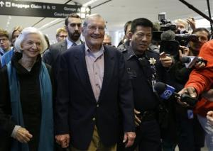 Merrill Newman, center, walks beside his wife Lee after arriving at San Francisco International Airport on Saturday, Dec. 7, 2013.